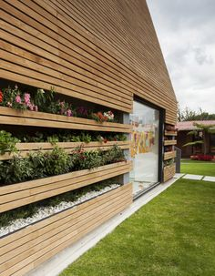 Designed by Lacaja Arquitectos with the supervision of Gloria Serna Meza, the bold and simple form is clad in horizontal timber slats cleverly incorporating a flower garden within. One face (seen above) features a large powdercoated black steel framed window displaying the children's colourful artwork