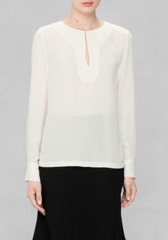 Flowy crepe fabric is crafted into this slightly demure blouse featuring a keyhole detail with hook closure at front.