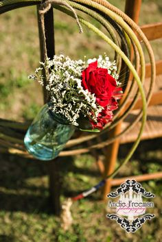 Lasso pew marker with red roses, teal lilies, and baby's breath in blue mason jar hanging from horseshoe.  Country Western fall wedding in barn. Photography: Andie Freeman Photography, www.TheAthensWedd... Venue: The Barn on Belmont; thebarnonbelmont.... Event Design and Floral: Hydrangea House Make-up:  Bombshell Creations www.BombshellCreations.com