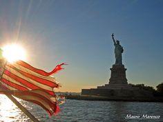 New York, la statua della libertà con la bandiera americana al tramonto