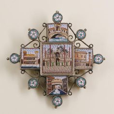 A 19th century micro mosaic cross pendant/brooch depicting Venetian scenes, the central panel of St Mark's Basilica, with four surrounding panels depicting the Bridge of Sighs, the Doge's Palace and St Mark's column, the Rialto bridge, and a palazzo on the Rialto, gilt metal mounted, with eight round floral mosaics between,length 4.5cm.