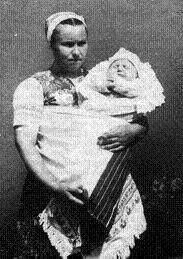 """a Nyitra megyei Zséren készült 1958-ban, az anya egy ünnepi """"hosszúkeszkenyőben"""", vagy """"tácsiban"""" hordja babáját."""