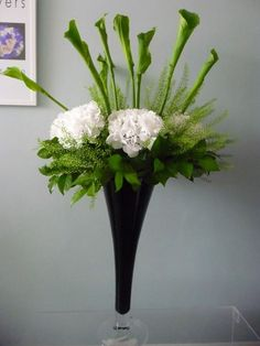 Contract flowers    Large stylish vase of 'Green Goddess' calla lilies and white hydrangea.
