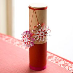 Give a wine-bottle holder new life with pretty trim and hanging flowers! http://www.bhg.com/christmas/gift-wrapping/gift-wrapping-ideas/?socsrc=bhgpin121214paperflowers&page=2