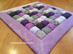 This purple and gray baby bubble puff quilt is both elegant and sweet - perfect for your little one! This READY TO SHIP quilt is ideal for floor time and makes an excellent travel blanket so your little one always has a soft and comfortable place to lay.  This quilt is handmade and measures approximately 37 inches by 37 inches. Each of the 64 hand stuffed puffs are made with 100% cotton fabric and stuffed with poly-fill. This quilt is incredibly soft. It is bordered with a soft purple dotted…