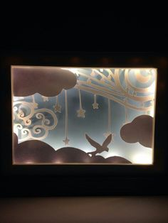 3D LED cloud bird frame. The Led lighting gives the design a shadowed effect as it reflects of all the layers. The design was hand drawn and intricately crafted together which makes each piece unique. This product can be used as a simple home decor item or a beautiful night light. The design comes with an alluring self standing black box frame with battery powered LED lighting.
