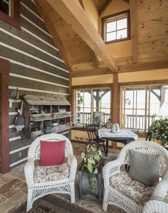 A cathedral ceiling, exposed beams, and plenty of windows for natural light give this log home's sunroom an open, airy feeling. #loghomes #logcabins #sunrooms