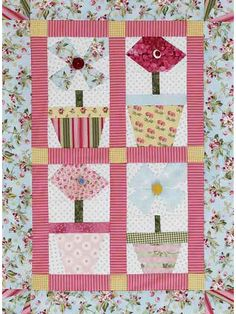 Feminine Floral Quilt    This girly wall hanging quilt frames four floral blocks inside a flower-pattern border.