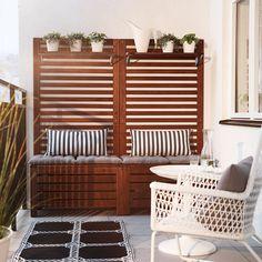 Balkong med förvaringsbänkar i brunt trä med sittdynor, väggpaneler och hyllor fyllda med gröna växter