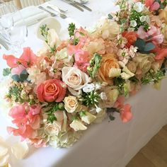 Coral and peach top table flowers at Nonsuch Mansion. Peach stocks, miss piggy roses, vendella roses, peach avalanche roses, peach and coral sweet peas. Surrey wedding flowers by Boutique Blooms floral design.