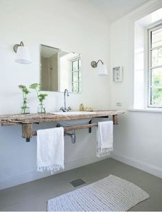 Simple, beautiful bathroom with a frameless beveled mirror illuminated by a pair of nickel sconces with pleated white shades over a rustic, wall mounted wooden vanity with built-in towel rail finished with a porcelain sink and gooseneck faucet over gray floors layered with a chunky, white knit rug.