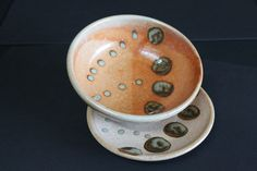 Bowl & plate.  WSO clay.  Carbon Trap Shino base.  Dipped half of bowl in CTS again.  Used round sponge to dab Woo Woo Blue circles and eye drops bottle to make dots.  Same glaze, same firing, but maybe different part of kiln?