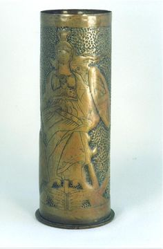 """Shell casing flower vase made from German 77mm shell. Engraved figure of Britannia with shield and lion at her feet with embossed background.  Reverse with dates in two roundels '1914' '1919' Shell dated September 1915 on headstamp. 9""""tall."""