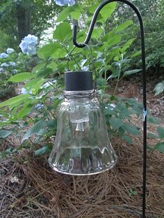 Old glass sconce globe, a cheap $1 solar light (stake removed), some wire and a shepherds hook. Easy and cheap landscape lighting.
