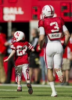Nebraska's Taylor Martinez (3) guides Jack Hoffman, 6, of Atkinson, down the field for his touchdown play during a special segment dedicated...