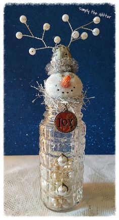 Lizzie is made using a vintage glass salt shaker filled with vintage faux pearl beads and mica flakes. Her hat is made out of a salt shaker lid with pearl decoration. Around the edge is silver garland trim. Her scarf is silver eyelash trim and rhinestone trim with a little charm that says Joy. On the front are 2 pearl buttons.  Her head is sculpted from paper clay and the eyes are small metal brads. Lizzies carrot nose has been formed out of Fimo clay and a diamond dust glitter has snowed…