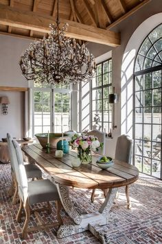 Country vibe from exposed beams and rafters and dining table in unfinished wood plus bricks for flooring. Simple elegance from the chairs, classic French windows and doors; French Country Dining Room, French Country House, Country Chic, Dining Room Table Decor, Dining Room Design, Dining Tables, Coffee Tables, French Decor, French Country Decorating