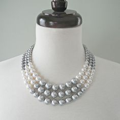 El collar de bloqueo Color cuenta con una silueta clásica con color atrevido de bloqueo, lo que es perfecto para la mujer moderna con estilo atemporal. Este collar características lujosas Austria cristal perlas en gris, blanco y plata, dispuestos en un motivo de bloqueo. Forma cónica de tamaños graduados, de 6mm a 12mm de perlas. El collar sujeta con un broche de gancho plateado plateado. El nivel menor es 18 pulgadas de largo. Su collar está empaquetado en una firma crujiente blanco…