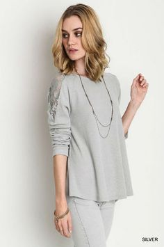 Silver long sleeve lace knit top. Lace panel on shoulders and back. Fabric: 60% Cotton 40% Polyester. Hand wash only. Hang or line dry. Do not bleach.