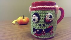 This is one in a series of Halloween Mug Cozies. The mugs used in this series were purchased from the local Dollar Tree. This Zombie Cozy is worked from bottom to top, joining side below the mug handle. A tab is created on the edging to clasp above the mug handle. The face details are hand sewn on last.