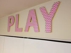 My first Mod Podge project! $1 cardboard letters from Hobby Lobby. Pink chevron scrapbook paper mod podged on. Painted the sides yellow and attached hooks to hang. Total price for playroom wall art, less than $10!