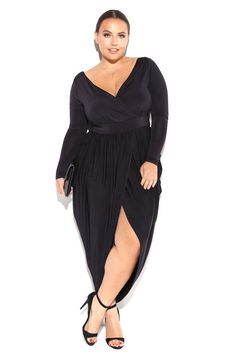A plus size midi wrap dress with a V neckline and long sleeves. Features a cinched waist and a ruched wrap skirt. Solid colored.