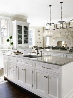 Gray countertops and darker floors help balance white…