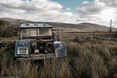 // An old Land Rover sits on the land, completely wrecked, outside the abandoned Welsh farmhouse which has been empty for decades.
