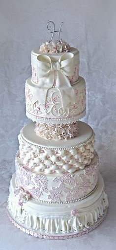 All white wedding cake (tiny touches of pink) with 6 layers of varying sizes…