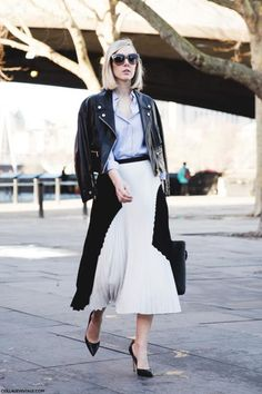 The Midi Skirt and Leather Jacket Combo Is One Youll Want to Try ASAP - black and white accordion pleat midi skirt worn with a blue button-down + over-the-shoulder cropped leather jacket and classic pointy toed pumps