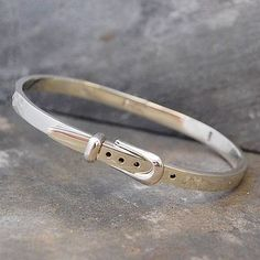 Flat wire bands hand-crafted to look like a belt are connected by a hinge mechanism which locks closed the bangle with an ingenious silver buckle. #Otisjaxon #Jewellery #Accessories #Bangle #Women