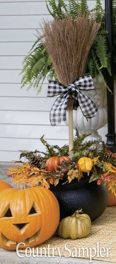 Use a witches' cauldron to form the base of a cute porch display. Place a block of floral foam in the cauldron and surround by stones to weight the piece down. Stick a straw broom in the center and accent it with a bow. Fill in the top of the cauldron with greens, leaves and real or faux gourds and pumpkins.