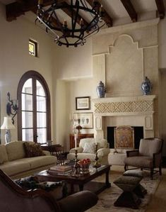 The fireplace, wooden beams in the ceiling, chandelier, and casual style