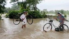 Baksa Villagers carry their bicycles as they wade through a waterlogged Barma area in Baksa district of Assam.