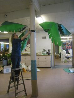 making a tree    Green paper leaves, with coat hanger stems, brown balloon coconuts, corrugated cardboard wrapped pillar trunk. One of four.
