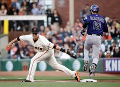 San Francisco Giants first baseman Buster Posey, left, comes off the base while catching an errant throw from second baseman Joe Panik, allowing Colorado Rockies' Charlie Blackmon (19) to reach first base safely during the first inning of a baseball game Monday, Aug. 25, 2014, in San Francisco. (AP Photo/Marcio Jose Sanchez)