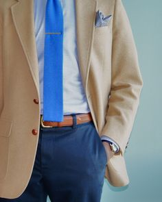 Great summer look pairing a beige camel hair sports coat with bright blue knit tie and silver tie bar. We also like the combination of subtle check patterned shirt with glen-check pocket square.