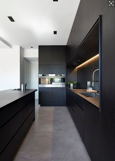 kitchen idea - M House is a minimalist house located in Melbourne, Australia, designed by DKO. The kitchen space features blacked out custom cabinetry with a black kitchen island that allows for seating and serving. Kitchen Decorating, Home Decor Kitchen, Kitchen Furniture, New Kitchen, Kitchen Dining, Kitchen Ideas, Awesome Kitchen, Kitchen Layout, Concrete Furniture