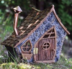 The Shingletown large pitched roof is a crooked looking wood sided fairy house. It has a bent chimney and slanted windows and doors. The door opens and closes.