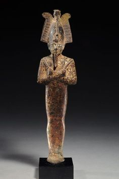 EGYPTIAN GILT BRONZE OSIRIS WITH SILVER INLAID EYES Mummiform, wearing the atef-crown and holding the crook and flail. XXVIth Dynasty, 664-525 BC