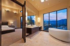 A modern bathroom featuring a floating vanity and curved soaking tub has a stunning view of the mountains. Source: http://www.zillow.com/digs/Home-Stratosphere-boards/Luxury-Bathrooms/