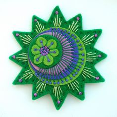 Free-form embroidery on felt for a pin or brooch by APPLIQUE-designedbyjane on flickr.