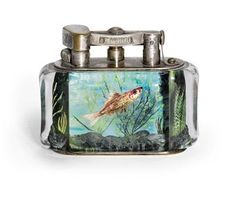 AN 'AQUARIUM' TABLE-LIGHTER  BY DUNHILL, 20TH CENTURY  The lucite panels internally decorated with fish within coral and seaweed, the metal fitments signed 'Dunhill'.