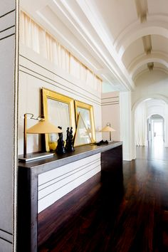Hallway with dark wood floors, gold mirrors, gold lamps, and white walls