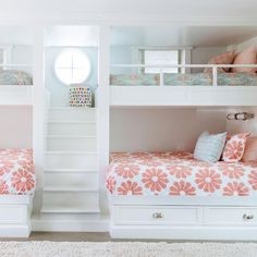 Girls' bunk room features a built-in staircase flanked by built in bunk beds dressed in pink and turquoise bedding.