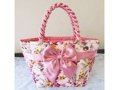 The lovely pink bundle little flower zip bow bag is a handmade pink cotton fabric with flower pattern. For the exterior, it is a very attractive bag with beautiful pink cotton fabric including with pink satin bow and double twisted bag handle. For the interior, not only it is lined with plastic polyester that is good for waterproof but also it has a PVC bag bottom support to give the bag great stand-up and posture. So it is a gorgeous pink bow bag with lightweight and Eco- friendly cotton…