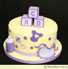 This cute baby shower cake was based on a popular previous design, incorporating baby blocks, bibs and bottles. For an expecting mother who is having a Unique Baby Shower Cakes, Baby Shower Cake Designs, Simple Baby Shower, Baby Shower Purple, Purple Baby, Baby Reveal Cakes, Unisex Baby Shower, Different Cakes, Baby Blocks