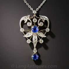 Edwardian Sapphire and Diamond Pendant. A sweetly stylized heart motif is elegantly designed and hand fabricated in silver over gold in this delightful antique jewel dating from the-turn-of-the-twentieth century. The necklace sparkles with an array of old mine and rose-cut diamonds and features a gorgeous pair of true blue round faceted sapphires, one in the center and the other dancing below. The pendant measures 1 5/16 by 13/16 inches, the chain is platinum and measures 17 inches.