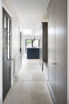 Contemporary Family Kitchen, Chelmford, Essex - Humphrey Munson Kitchens - Dark blue island, grey cabinetry, metallic lighting, georgian doors, babington limestone flooring