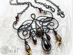 This decadent, cold-forged copper necklace was inspired by the ironwork balconies of New Orleans and the ironwork galleries at the Victoria and Albert museum in London. I have used a deep charcoal patina on the copper to give an old, iron feeling to the metal. The patina has been sealed in museum-quality Renaissance Wax. The whorls of this necklace are accented by a carnelian stone bead, Czech glass drops and Swarovski crystals. If Galadriel were to move to the Big Easy, maybe she would wear…